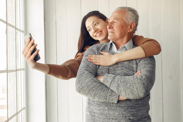 Элегантный старик стоит дома с внучкой