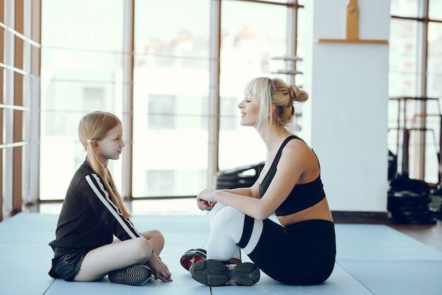 Мать и дочь занимаются йогой в студии йоги