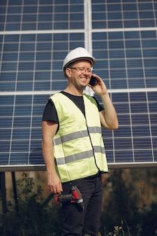 ソーラーパネルの近くの白いヘルメットを持つ男