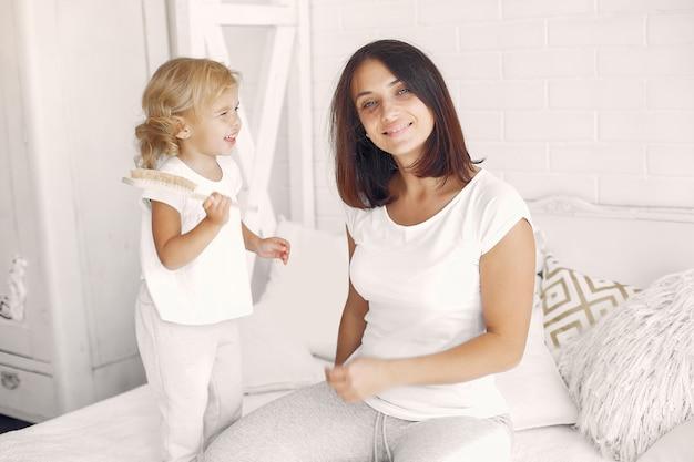 彼女の母親の髪をとかす小さな娘