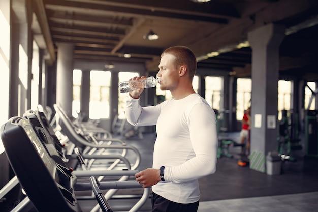 ハンサムな男は、ジムでトレッドミルで水を飲む