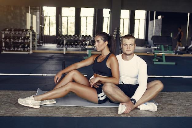 ジムでスポーツウェアトレーニングのスポーツカップル