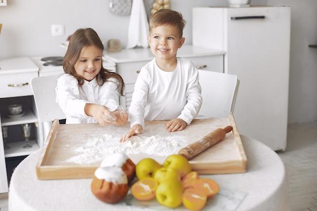 Симпатичные маленькие дети, сидя на кухне с тестом