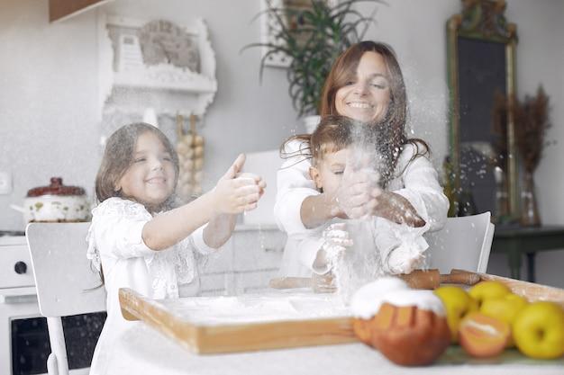 Семья сидит на кухне и готовит тесто для торта
