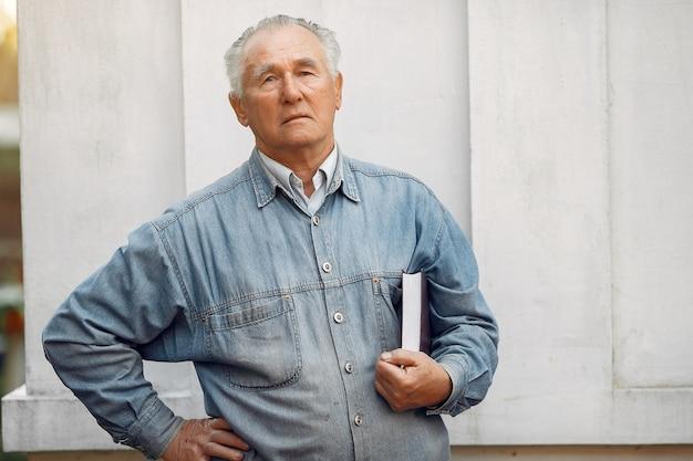 Элегантный старик стоит с книгой