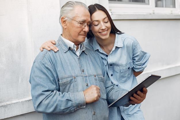 Молодая женщина учит своего деда, как использовать планшет
