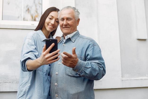 Молодая женщина учит дедушку, как пользоваться телефоном