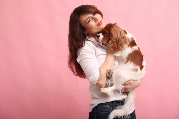 ファッションの若い女性が犬とポーズ