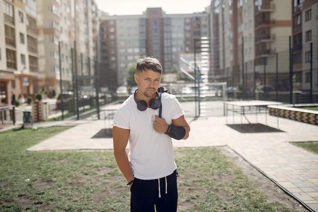 Красивый мужчина стоял в парке с наушниками
