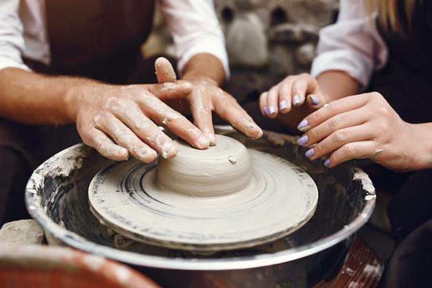 カップルは花瓶を作る茶色のエプロン