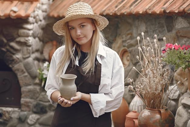 手作りの花瓶を保持している女性