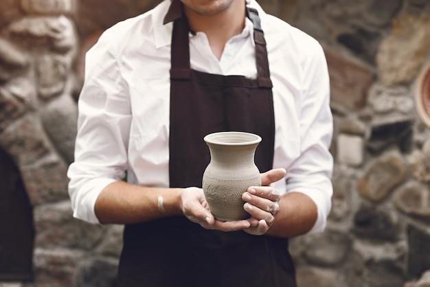Человек в коричневом фартуке стоит с вазой