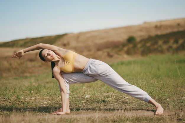Симпатичная девушка тренируется в поле