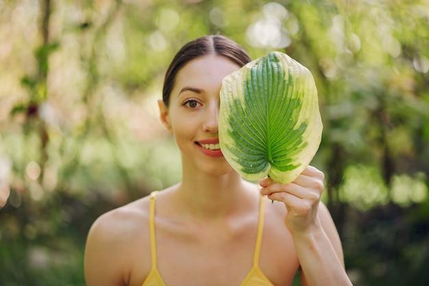 彼女の顔の近くの緑の葉を保持している女の子