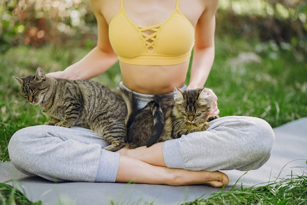 Девушка сидит в парке летом с милой кошкой