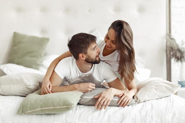 Пара сидит на кровати в комнате