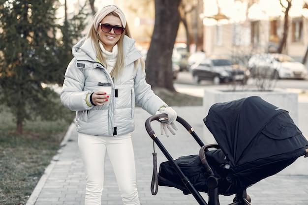 Стильная женщина гуляет по городу с коляской