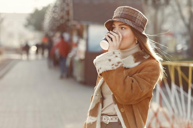 春の街を歩いて、コーヒーを飲んでいる女の子