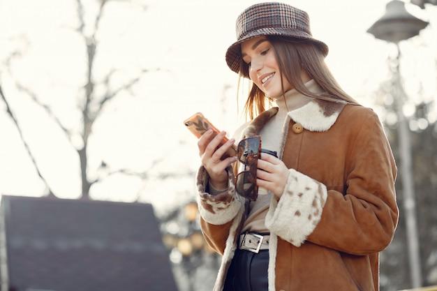 春の街を歩いて、電話を使用して女の子