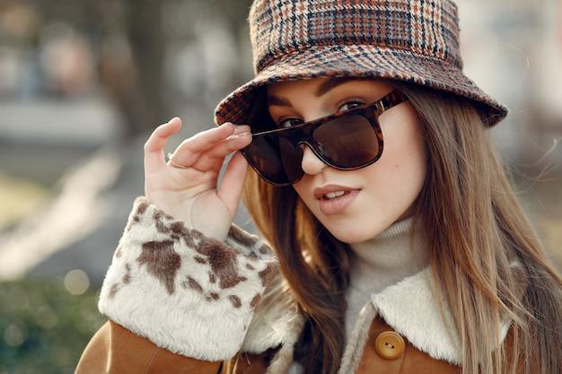 Девушка в солнечных очках смотрит в камеру