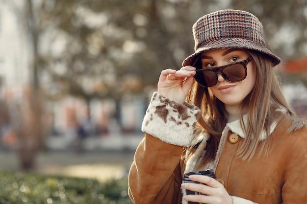 春の街を歩いて女の子と彼女の手でコーヒーを保持