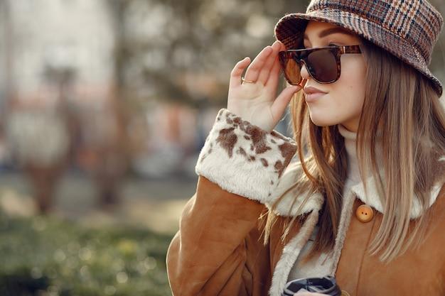 Девушка гуляет в весеннем городе и принимает кофе