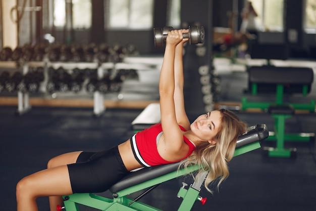 Спортивная блондинка в спортивной тренировке в тренажерном зале