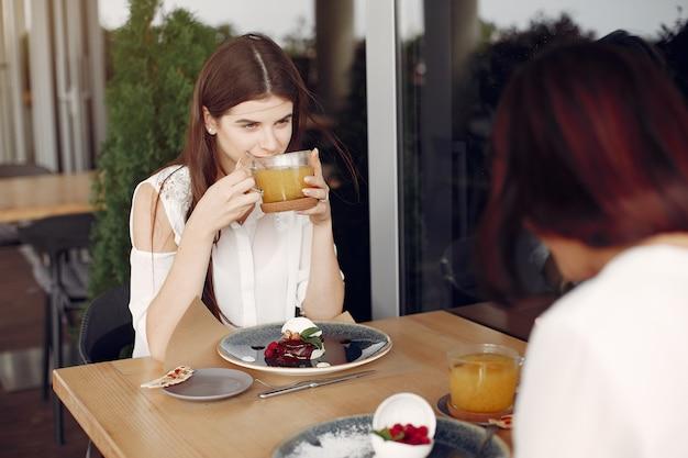 Мать с взрослой дочерью сидит в кафе