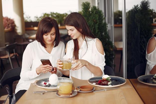 Мать и взрослая дочь, сидя в кафе