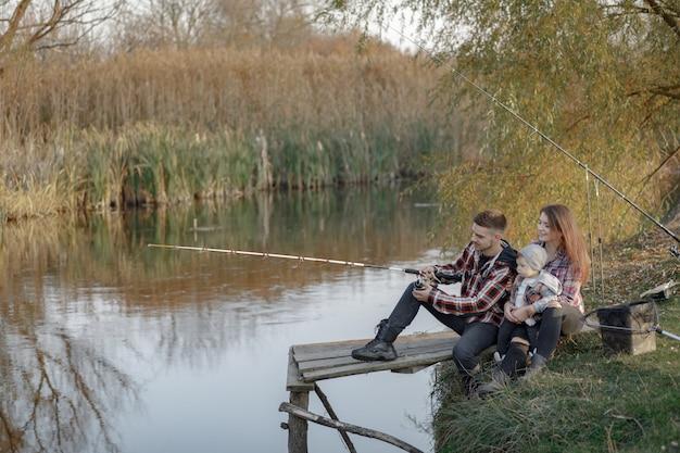 Семья сидит возле реки в рыбалку утром