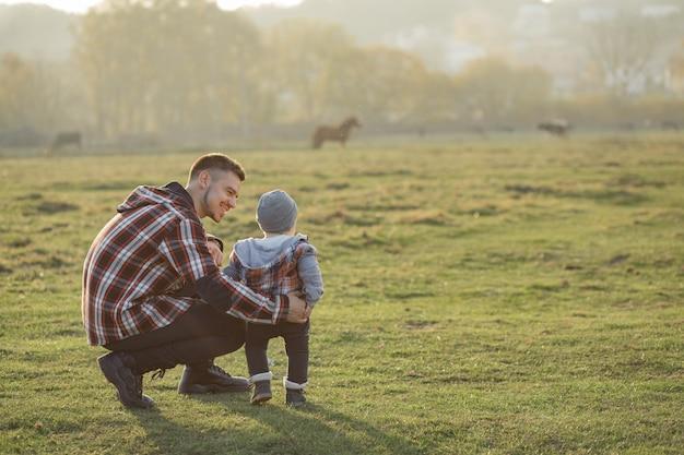 朝の野を歩く幼い息子を持つ父