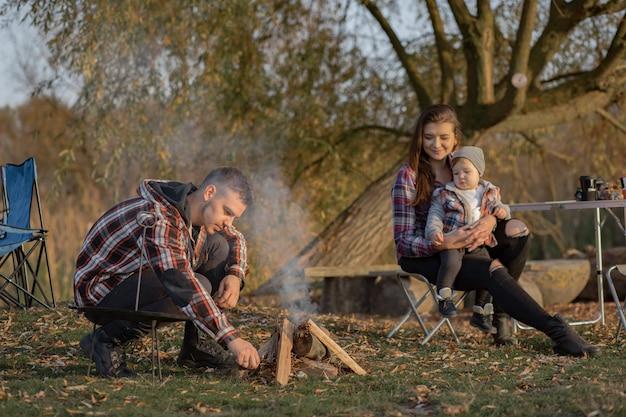 Милая семья сидит на пикнике в лесу