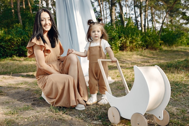母と幼い娘が夏の畑で遊んで
