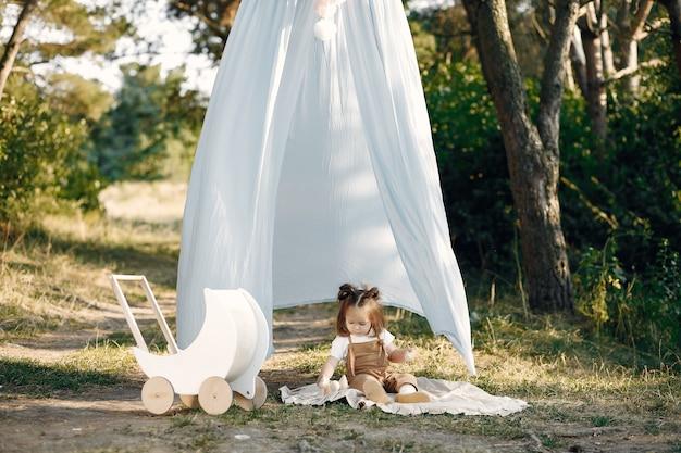 Милая маленькая девочка, играя в парке с белой коляской