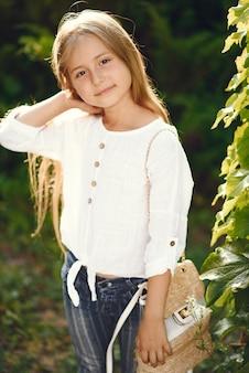 Маленькая девочка в парке стоит с коричневой сумкой