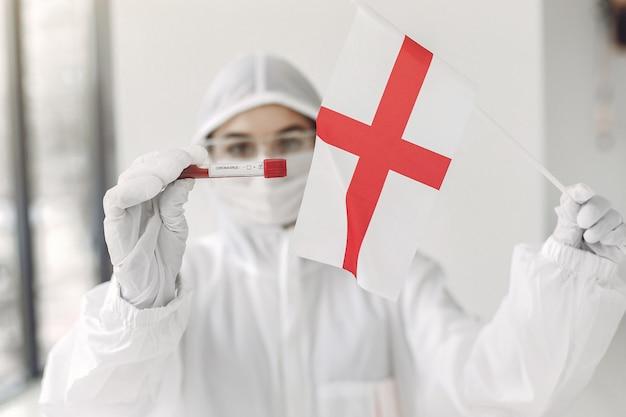 コロナウイルスのサンプルと英語のフラグを持つつなぎ服の科学者