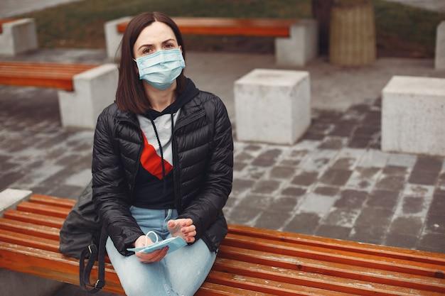 使い捨てマスクの女性が子供にマスクを着用するように教えています