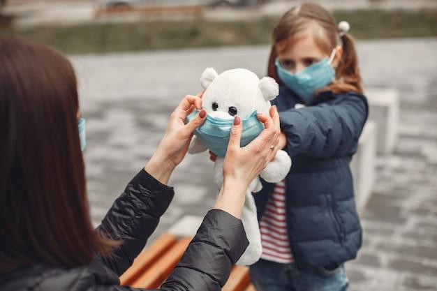 Женщина в одноразовой маске учит ребенка носить респиратор