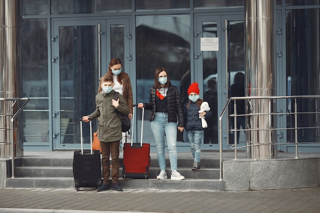 Путешественники, покидающие аэропорт, носят защитные маски