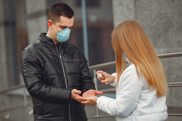 保護マスクを身に着けている若者は手の消毒剤を噴霧しています。