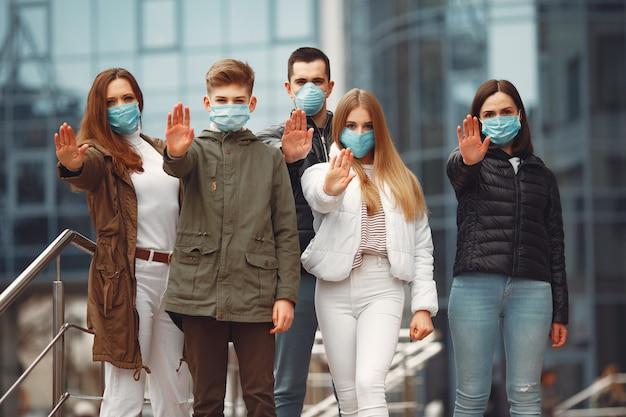 保護マスクを着用している人は、手で一時停止の標識を見せています
