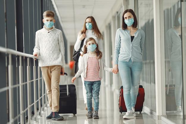 空港の人々は、ウイルスから身を守るためにマスクを着用しています