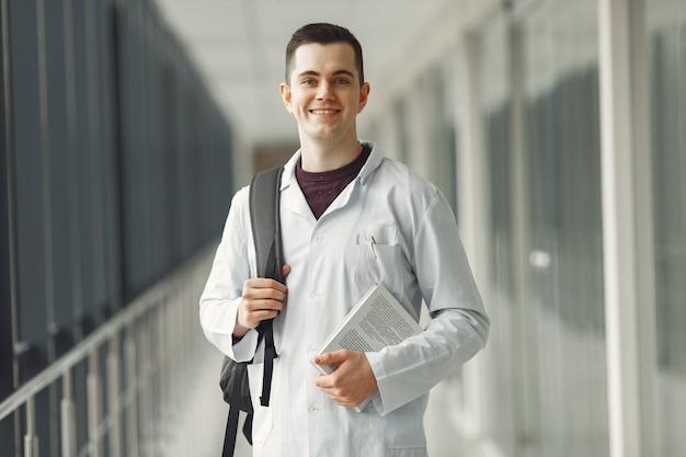 バックパックで医学生が近代的な診療所に立っています。