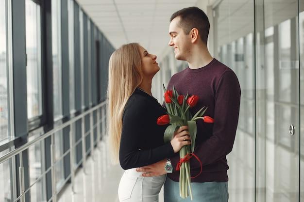 ヨーロッパのカップルは赤いチューリップの束とホールに立っています。