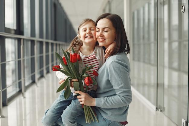 娘が母親に赤いチューリップの束を与えています