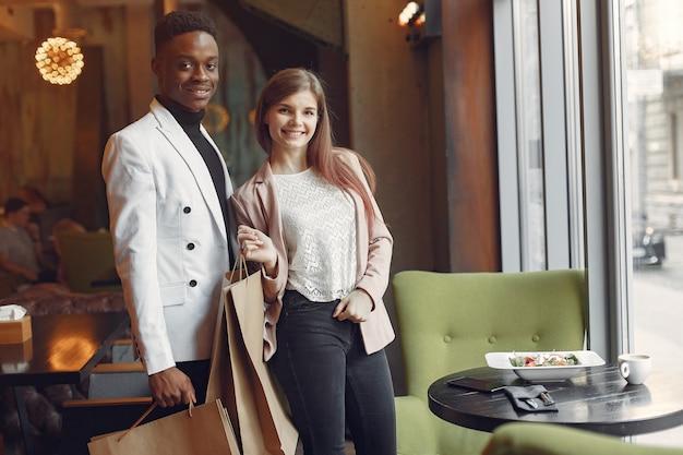買い物袋とカフェに立っている国際人