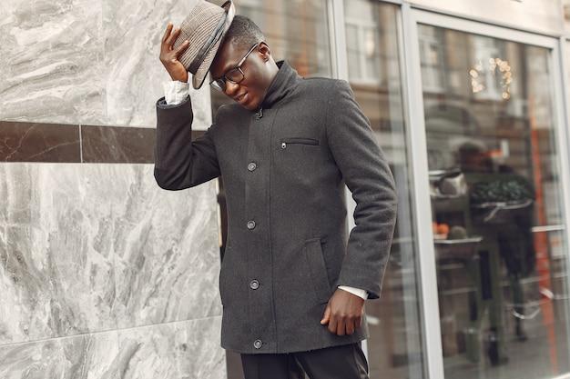 秋の街で黒いコートを着た黒人男性