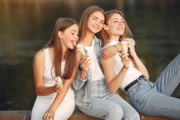 Девочки гуляют по весеннему городу и держат в руках мороженое
