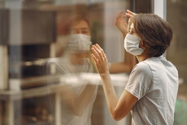 マスクの女性が窓のそばに立つ
