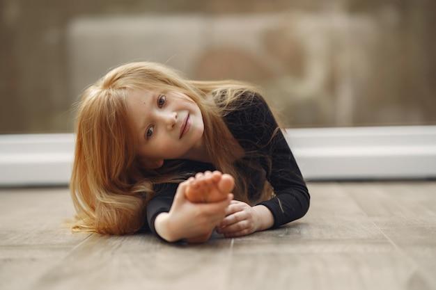 Маленькая девочка в черной спортивной одежде занимается гимнастикой